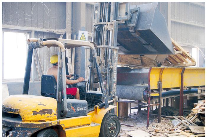 工人正在给破碎机加料,全流水线机械作业